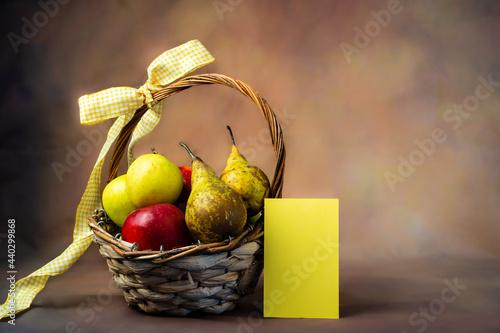 Fototapeta Scena con un cesto di frutta pieno di mele e pere rosse e gialle legato con un fiocco giallo con un biglietto di auguri giallo acanto su sfondo marrone