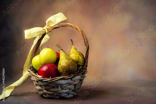Fotografie, Obraz Scena con un cesto di frutta pieno di mele e pere rosse e gialle, legato con un fiocco giallo