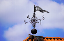 Old Metal Weather Vane On The Roof Of A Building With The Four Cardinal Points. Blue Sky In The Background.