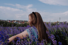 Smiling Young Woman In Denim Jacket Touching With Hand Purple Flowers Standing Alone Among Field Enjoying Of Sunlight At Golden Hour. Summer Outfit. Girl With Flowers. Having Fun Outdoors