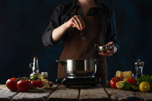 A Chef In A Dark Uniform Prepares A Vegetable Soup. Here, The Chef Is Adding Salt To A Stainless Steel Pot On A Wooden Table. There Are Many Ingredients For Making Soup Around. Dark Blue Background.