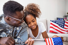 Portrait Of Happy American Family Father In Military Uniform And Cute Little Girl Daughter With Flag Of United States Hugging And Smiling At Camera, Male Soldier Dad Reunited With Family At Home