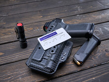 Concealed Carry Permit Laying On Handgun In Holster With Spare Magazine And Hand Light