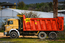 Dump Truck With The Image Of The National Flag Of China Is Parked Against The Background Of The Countryside. The Concept Of Export-import, Transportation, National Delivery Of Goods