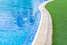 Wide Swimming Pool And Green Artificial Turf Inside The Villa