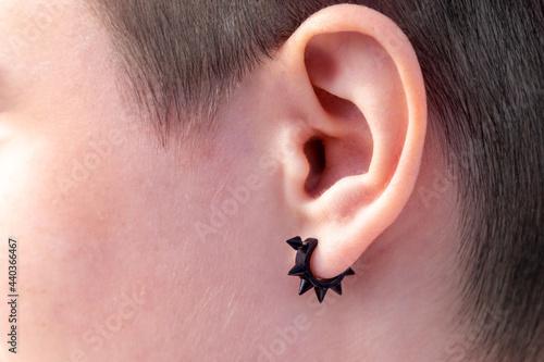Billede på lærred Black earring in the ear close-up, ear piercing
