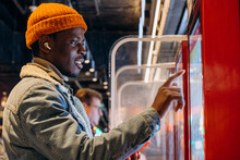 Positive African-American Guy In Orange Knitted Hat With Wireless Earphones Orders Food Through Self-service Kiosk In Cafe