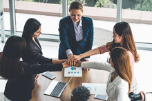 Businesswomen Joining Hands In Group Meeting At Modern Office Room Showing Teamwork, Support And Unity In Work And Business. Female Power And Femininity Concept.
