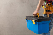 Man Worker Holding Toolbox And Tool Belt Near Wall. Male Hand And Construction Tools
