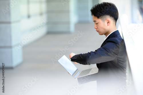 Fototapeta パソコンを操作しながら時間を確認するビジネスマン