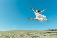 空と白いワンピースの踊る女性(ジャンプ)
