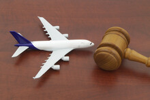 Wooden Judge Gavel And Airplane Model On Wooden Background.