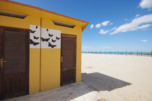 In The Foreground The Changing Room With Yellow Wall And Black Butterflies On A White Background, In The Distance The Beach Before Summer And The Sea.