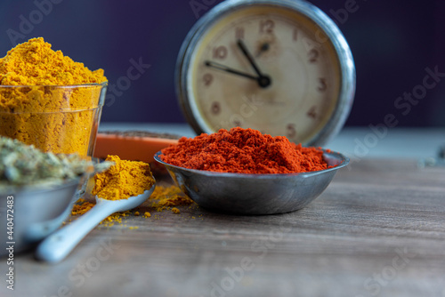 Fotografie, Obraz Colorful culinary spices and clock on wooden surface