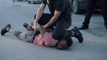 Policeman Putting Handcuffs On Crying Black Man