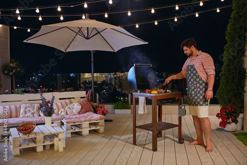 Fotografija a man grilling barbecue on rooftop patio, enjoys warm summer night at home court