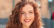 Leinwandbild Motiv Portrait of beautiful young girl of caucasian ethnicity with curly ginger hair standing on the warm spring city street dressed at the casual clothes during morning.