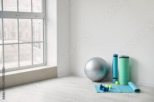 Fototapeta Set of sports equipment with fitness ball near light wall