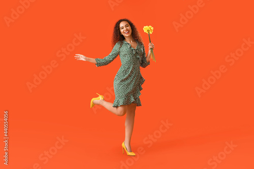 Photo Beautiful young African-American woman with narcissus bouquet on color backgroun