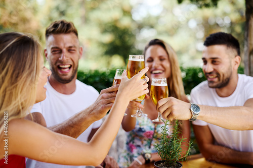 Group of happy friends toasting with beer at the summer bar фототапет