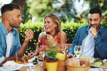 Group Of Young Happy People Having Lunch At A Restaurant During A Sunny Summer Day