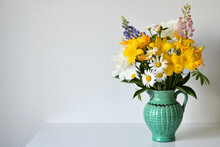 Summer Bouquet In A Jug Of Garden And Wild Flowers On A White Table Against A White Wall. Arrangement Consists Of A Bright Yellow Lilies, Daisies, Lupines. Selective Focus, Copy Space.