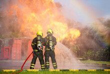 Two Firefighter Water Spray By High Pressure Nozzle In Fire Fighting Operation / Fire And Rescue Training School Regularly To Get Ready.