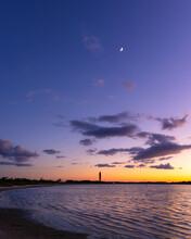 Crescent Moon In The Sky Above The Orange Glow Of Dusk. Jones Beach - Long Island New York