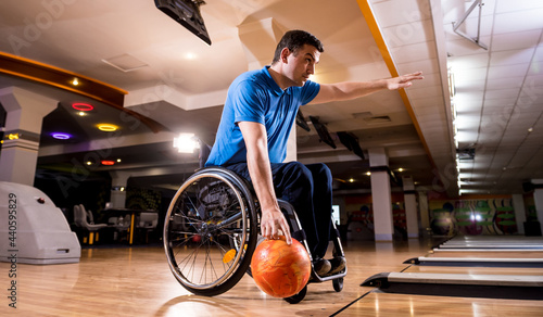 Fotografie, Obraz Young disabled man in wheelchair playing bowling in the club