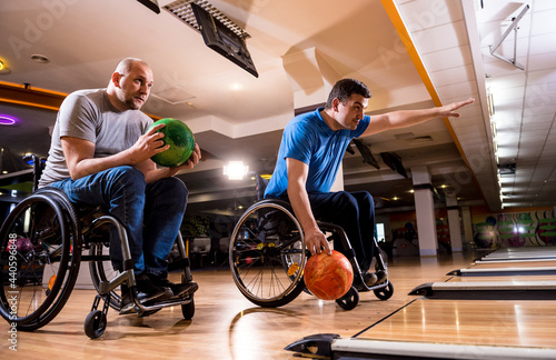 Two young disabled men in wheelchairs playing bowling in the club Fototapet