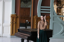 Young Woman On The Background Of The Piano In The Hall In The Art Deco Style