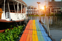 Colorful Of Rainbow Corridor, Wooden Bridge Is Walkway To Get On A Boat  In The Lake Or Lagoon With Waterfront Pavilion And House For Tourist To Travel.