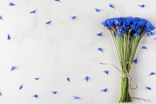 Blue Cornflowers. Summer Wildflowers Bouquet With Frame Made Of Blue Petals On White Marble Background. Top View