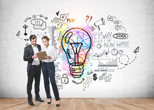 Businessman And Businesswoman In Formal Clothes Holding Clipboard And Brainstorming Nearby Concrete Wall With Colorful Business Idea Lightbulb Sketch. Concept Of Creativity And Start Up. Full Length