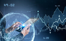 Businesswoman Hands And Finger Touch Tablet Display. Stock Market Changes Candlesticks, Data Information Icons And Rising Graph. Concept Of Finance And Technology. Globe And Digital Interface
