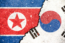 National Flags Of North Korea And South Korea On The Texture Of The Asphalt Surface With A Crack Between Them