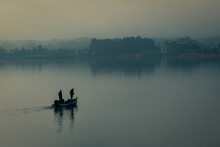 Silhouette Of Two Male Fisherman Sailing Boat In The Lake For Fishing With Landscape Of Wild Forest In The Background. Tree And Man Shadow Reflect On Water. Thick Fog In Morning With Blue Color Tone.