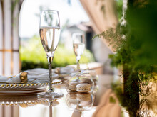 Exclusive Decoration Of The Banquet Table On The Terrace In The Luxury Restaurant. A Glass Of Expensive Champagne On A Gilded Chair.