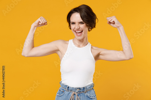 Young strong sporty fitness woman 20s with bob haircut wearing white tank top showing biceps muscles on hand demonstrating strength power isolated on yellow color background Fototapet