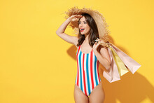 Side View Happy Young Sexy Woman Slim Body Wear Red Blue Swimsuit Straw Hat Hold Package Bag After Shopping Isolated On Vivid Yellow Color Background Studio Summer Hotel Pool Sea Rest Sun Tan Concept