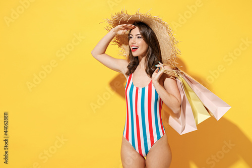 Foto Side view happy young sexy woman slim body wear red blue swimsuit straw hat hold