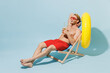 Leinwandbild Motiv Full length young blond man in red shorts swimsuit sit in deckchair near hotel pool hold inflatable rubber ring drink beer isolated on pastel blue background Summer vacation sea rest sun tan concept.