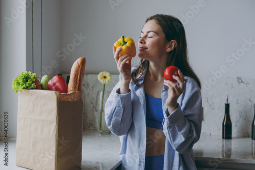 Tela Young happy satisfied vegeterian housewife woman 20s in casual clothes blue shirt hold tomato sniff bell pepper vegetables cooking food in light kitchen at home alone Healthy diet lifestyle concept