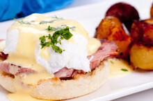 Closeup Shot Of Eggs Benedict With Farm Fresh Eggs And Ham And Fried Potatoes