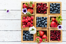 Top Down Close Up View Of An Arrangement Of Berries In Wooden Compartment Boxes Against A Light Wooden Table.