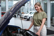 Female driver looking under car hood, choosing automobile to buy at the dealership