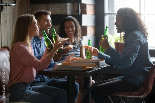 Murais de parede Overjoyed candid millennial multiracial diverse friends drinking beer and eating yummy pizza, enjoying pleasant conversation, communicating on weekend, enjoying leisure hanging out together in cafe