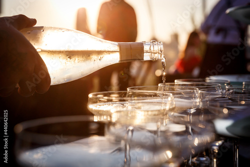 Tableau sur Toile Sunset closeup view of a Waiter's hand pouring sparkling wine into glasses at a party
