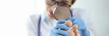 Dermatologist Examining Toenail With Magnifying Glass Closeup