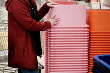 Woman In A Store Buys A Large Pink Container For Storing Things And Products. The Concept Of Buying Containers For Neat Storage Of Things